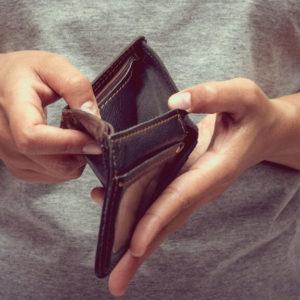 Человек держит в руках пустой кошелек
