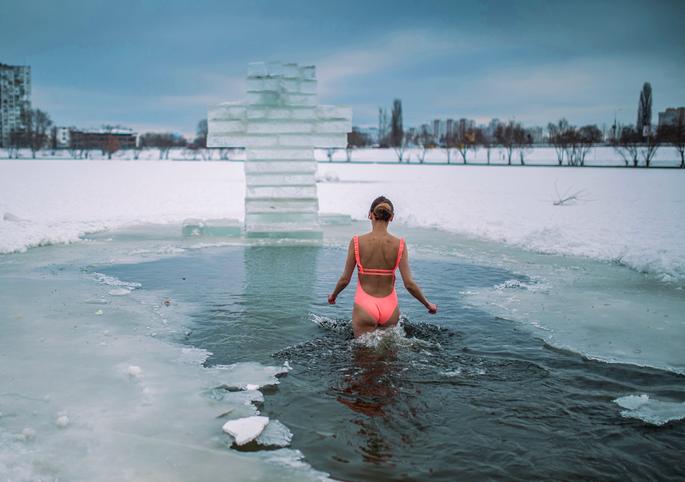 Молодая женщина в купальнике заходит в крещенскую прорубь