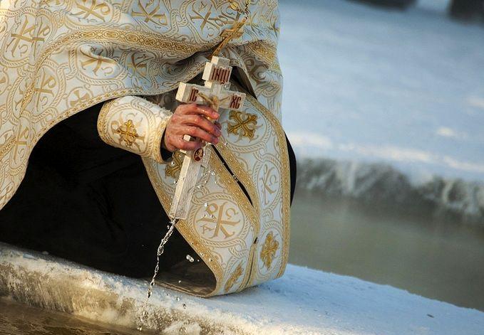Священнослужитель освещает прорубь