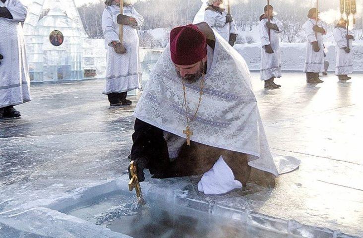 Священнослужитель святит воду в проруби