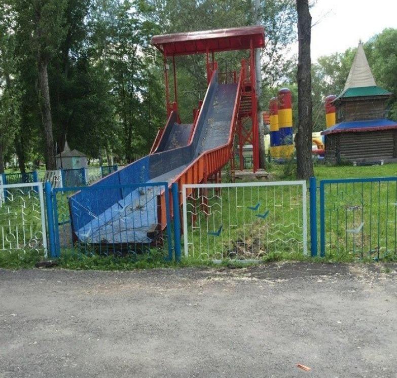 Детская горка со спуском, упирающимся в забор