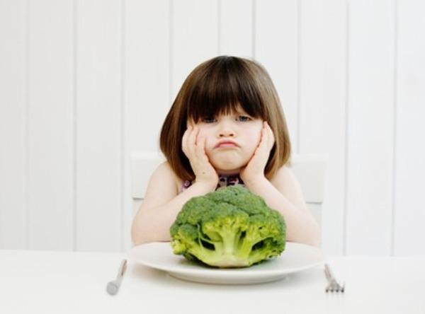 Недовольная девочка и брокколи на тарелке