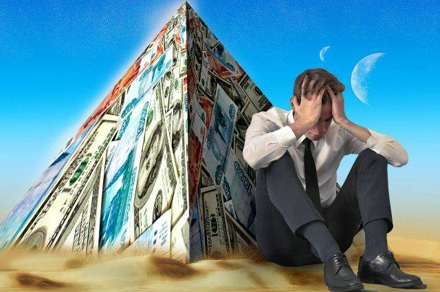 Человек сидит под пирамидой из денежных купюр обхватив руками голову