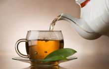 Чай из заварного чайника льется в чашку